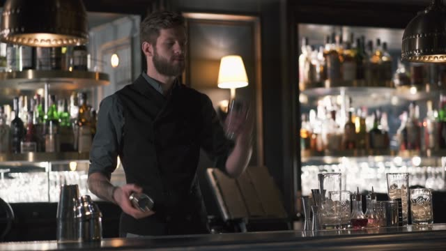 Attractive bartender professionally juggling cups and doing a show in beautiful modern bar. video