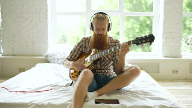 Attractive bearded man in headphones sitting on bed learning to play guitar using tablet computer in modern bedroom video