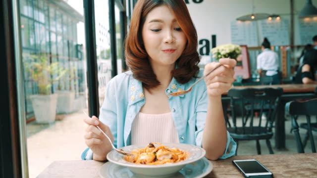 魅力的な美しいアジアの女性彼女の加入者とカフェとレストランで彼女のチャネルのスマート フォンやカメラの写真と記録作る食品ビデオブログ ビデオを使用して食品のブロガー。 ビデオ
