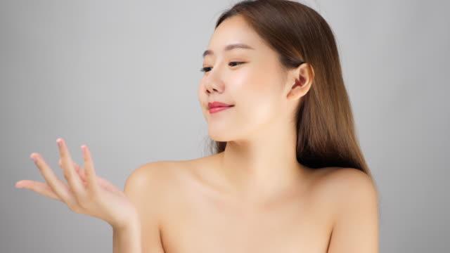 魅力的な美しい若いアジアの女性は美しさの顔の肌を持っています。かわいい女の子を示す魅力的な美しい女性の感動的な顔は、滑らかで明るい肌の顔をしています。女性オープンパーム、� - スキンケア点の映像素材/bロール