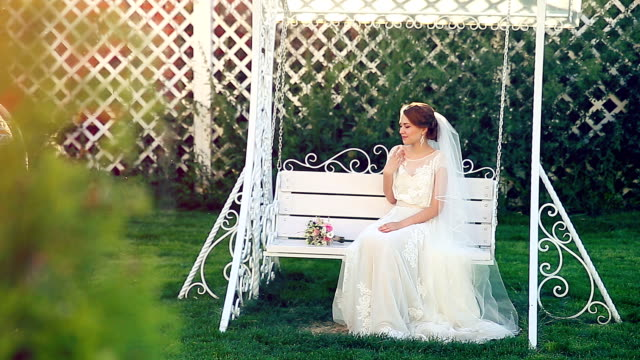 Attractive beauty bride on a swing under the sunset video