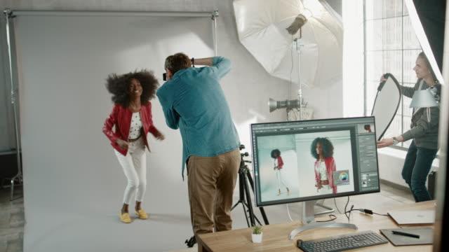 atrakcyjna czarna dziewczyna z bujnymi kręconymi włosami pozowanie do sesji zdjęciowej magazynu mody. zdjęcia zrobione przez słynnego fotografa. piękna dziewczyna uśmiecha się żartobliwie. sesja zdjęciowa made in professional studio - fotografika filmów i materiałów b-roll