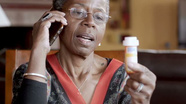 attractive black senior woman refilling her prescription on a smart phone - prescrizione medica video stock e b–roll