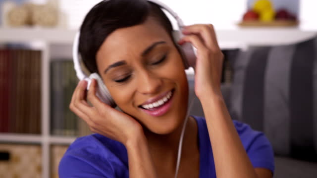 Attractive black woman listening to music and jamming out Attractive black woman listening to music and jamming out grooved stock videos & royalty-free footage