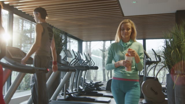 Attractive blond caucasian girl is drinking a protein shake drink while walking next to a treadmill in the sport gym. Attractive blond caucasian girl is drinking a protein shake drink while walking next to a treadmill in the sport gym. Shot on RED Cinema Camera in 4K (UHD). shaking stock videos & royalty-free footage