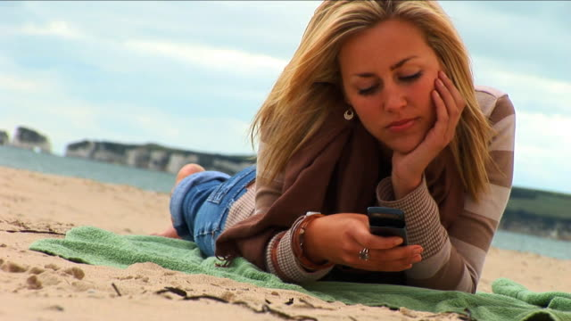 attractive blond girl texting on the beach - ligga på mage bildbanksvideor och videomaterial från bakom kulisserna