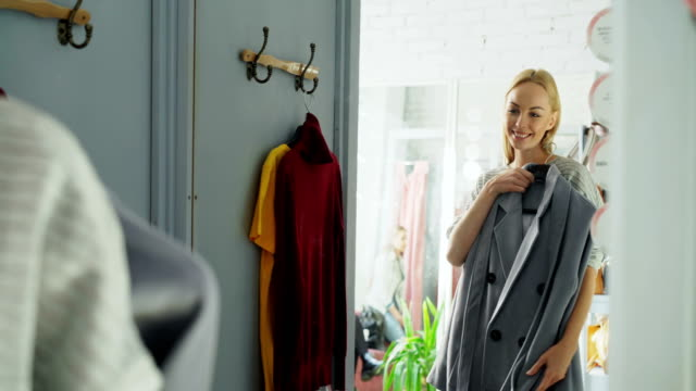 Attractive blond woman is trying elegant coat while standing in nice fitting room is clothing store. She is looking at herself in the mirror and smiling.