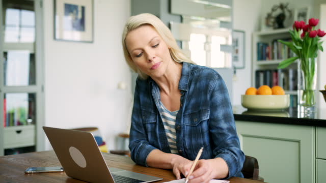 attractive blond woman typing on laptop and writing notes - trentenne video stock e b–roll