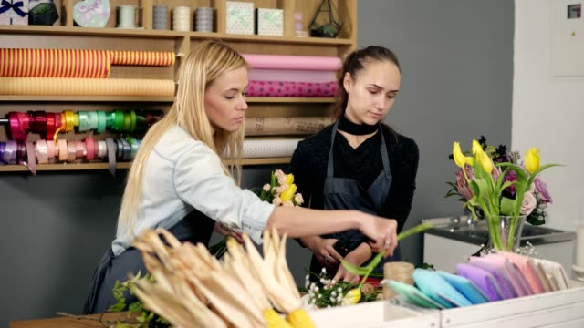 Attractive blonde florist in apron standing with her coworker at counter in floral shop while arranging bunch of flowers video