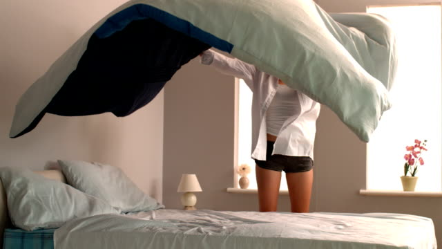 Attractive blonde giving the comforter a shake video