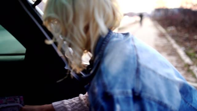 Blonde attirante dans une veste en denim parcourt ses sacs à provisions - Vidéo