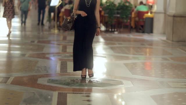 vídeos de stock, filmes e b-roll de loira atraente em salto alto e decorado em um vestido longo preto caminhando na noite em milão - moda parisiense