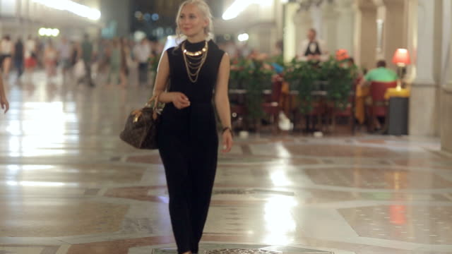 attractive blonde on high heels and dressed in a long black dress walks in the evening in milan - paris fashion stock videos & royalty-free footage