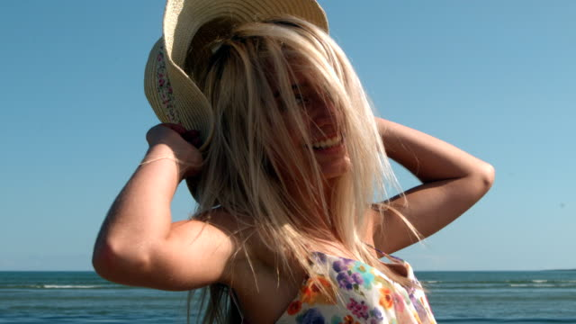 Attractive blonde turning with straw hat on beach video