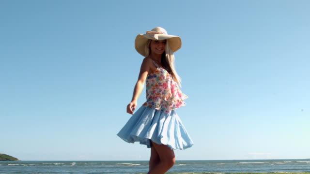 vídeos de stock, filmes e b-roll de loira atraente com chapéu de palha giros na praia - saia