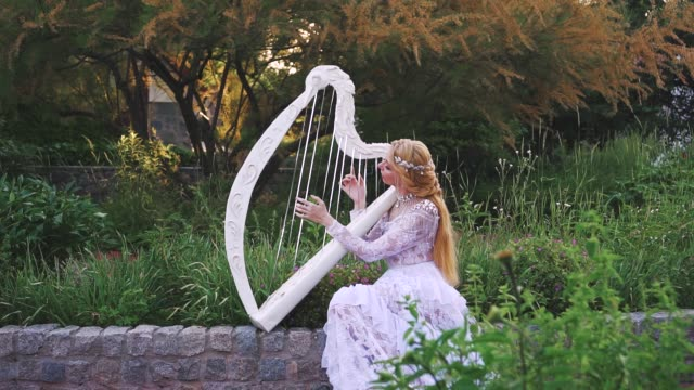 Attractive blonde woman in a white creative lace vintage dress plays the harp.