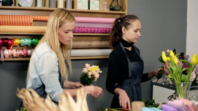 Attractive blonde woman in apron standing with her coworker at counter in floral shop while arranging flowers video