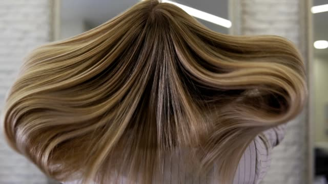 attractive blonde woman tossing her long, wavy hair indoors in slow motion - włosy filmów i materiałów b-roll