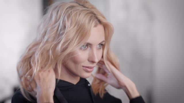 stockvideo's en b-roll-footage met aantrekkelijke blonde vrouw met mooie kapsel zichzelf in een spiegel kijken na schoonheid sessies - curly brown hair