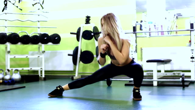 attractive blonde young woman warming up before training in a  gym. - donna forzuta video stock e b–roll