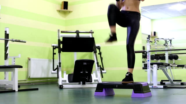 attractive blonde young woman warming up, jumping before training in a  gym. - donna forzuta video stock e b–roll