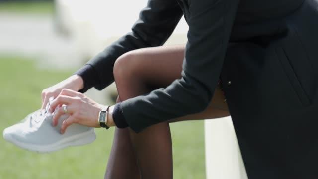 vídeos de stock, filmes e b-roll de fêmea atrativa do bolnde que muda em sapatas do esporte durante a ruptura do almoço - salto alto
