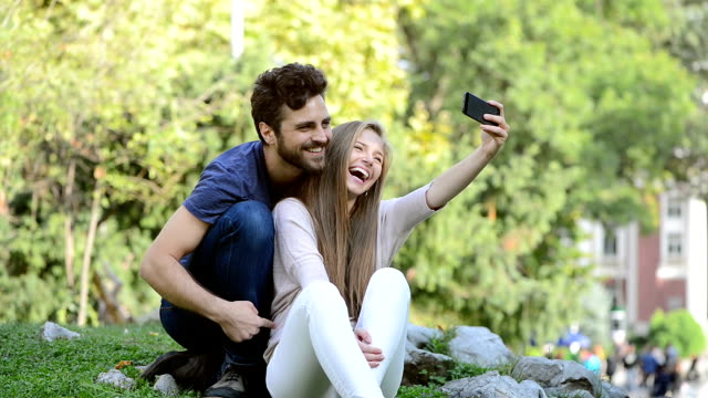 Attractive boy and girl couple taking selfie in park. video