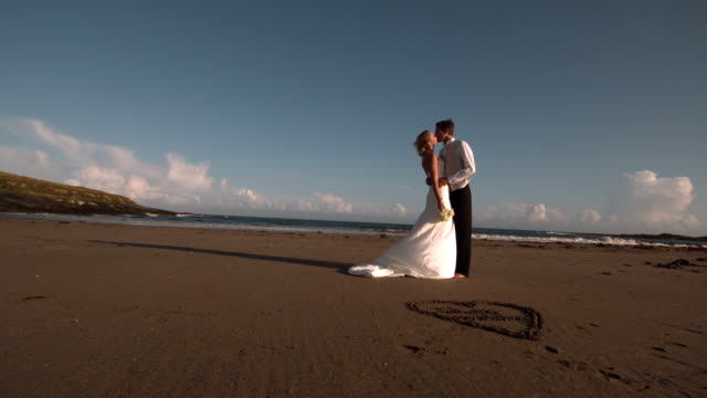 Attractive bridal couple kissing on the beach video