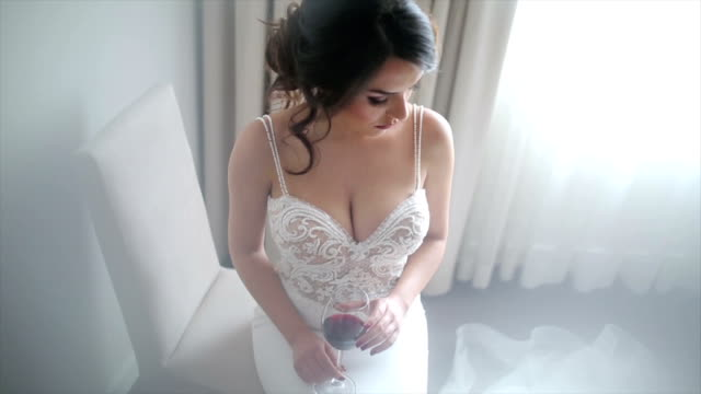 Attractive bride with a glass of wine posing in her wedding dress Attractive beautiful bride posing in her wedding dress seductive women stock videos & royalty-free footage