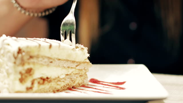 Attractive brunette eating a piece of cake in a cafe. Attractive brunette eating a piece of cake in a cafe. A nice woman is having breakfast in a restaurant. fork stock videos & royalty-free footage
