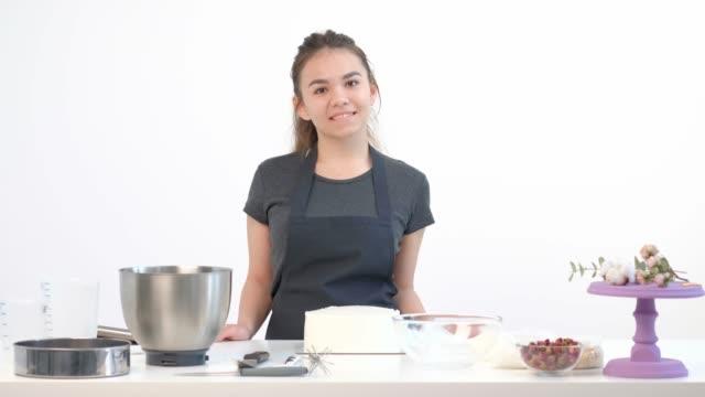 vídeos y material grabado en eventos de stock de atractiva morena chica chef pastelera en delantal látigo pastel de crema en un tazón de metal. - suflé