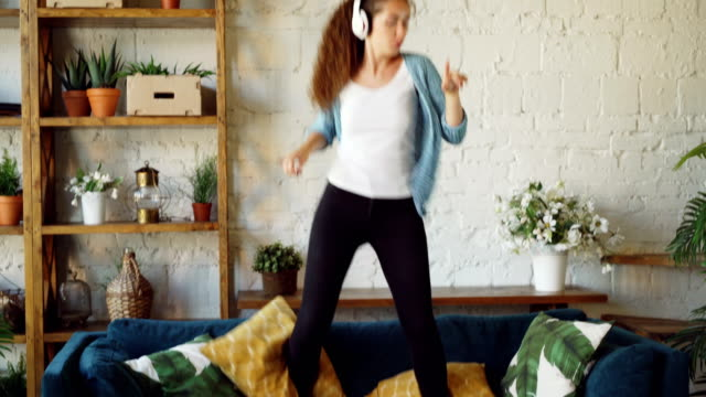 attractive brunette is having fun at home listening to music through headphones, singing and dancing jumping on sofa. modern technology and young people concept. - chudy filmów i materiałów b-roll