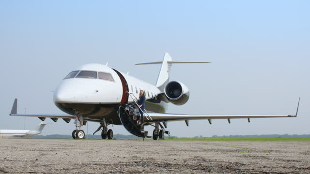 Attractive brunette smiles before boarding executive jet video