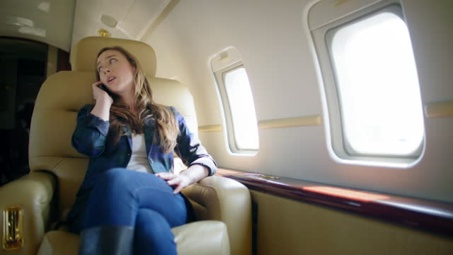 Attractive brunette using cellphone in comfortable seat on private jet video