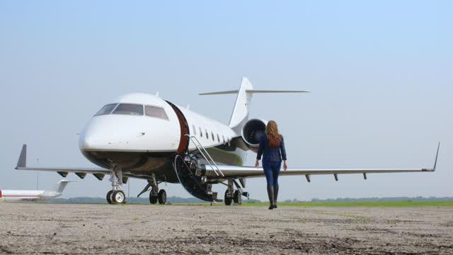 Attractive brunette walking towards an executive jet video