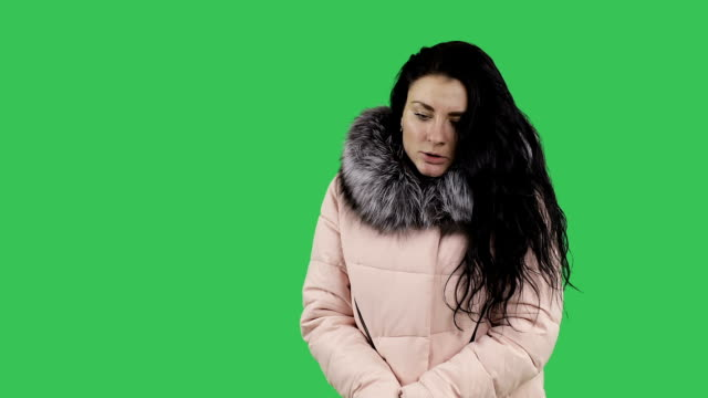 Attractive brunette with long hair in a winter coat freezes. video