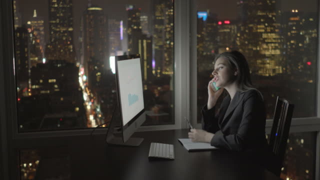 attractive brunette working at office table at night. businesswoman working with computer and smartphone in office with cityscape view. - capelli castani video stock e b–roll