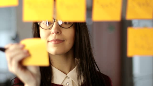 vídeos de stock e filmes b-roll de attractive business woman in glasses writes information on stickers and glues on the glass in the office. - writing ideas