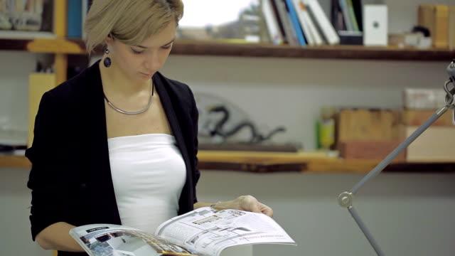 stockvideo's en b-roll-footage met aantrekkelijke zakenvrouw lezing tijdschrift in moderne kantoren - woman home magazine