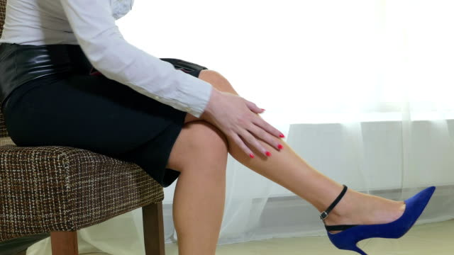 Attractive business woman rubbing tired feet while working video