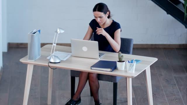 巨大なロフト スタジオで魅力的なビジネス女性使用ノート パソコン ビデオ