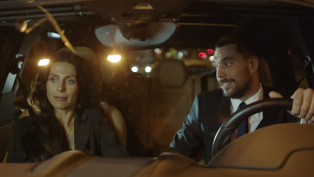Attractive Businessman and Woman Talking in a Car at Evening video