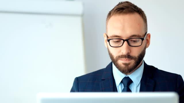 Homme d'affaires attrayant en costume et lunettes de travail avec ordinateur portable au bureau blanc - Vidéo