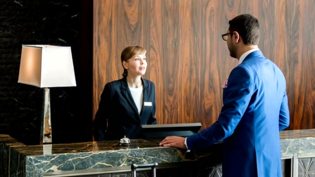 Attractive businessman registering at reception At reception desk. New handsome visitor wearing a blue suit and black glasses standing at reception while filling up a form to get the key to his hotel room checkout stock videos & royalty-free footage
