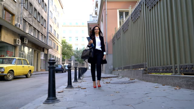 Attractive businesswoman walking on the street, holding file folder and fixing her eyeglasses video