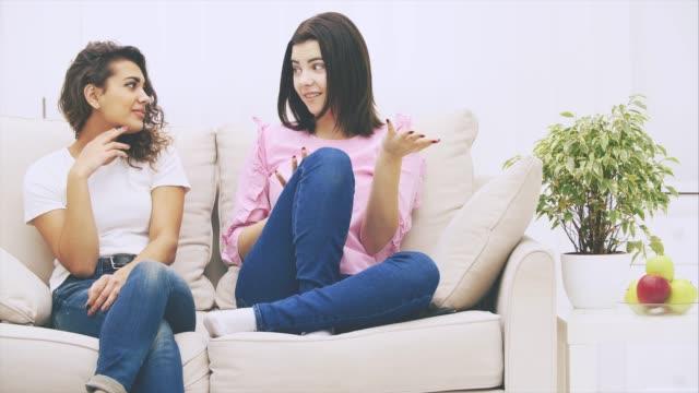 attraktiva kaukasiska flickan berättar sin afro-amerikanska vän en spännande historia. hennes vän lyssnar, ser förvånad och förvirrad. - kvinna ventilationssystem bildbanksvideor och videomaterial från bakom kulisserna