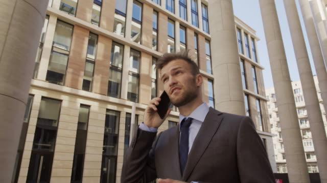 stockvideo's en b-roll-footage met aantrekkelijke blanke advocaat praten op telefoon buitenshuis - four lawyers
