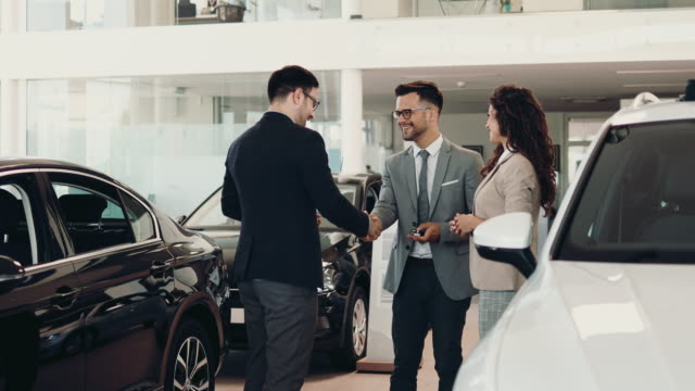 Attractive couple buying new car Middle age couple choosing and buying car at car showroom. Car salesman helps them to make right decision. car shopping stock videos & royalty-free footage