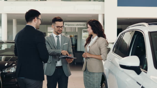 Attractive couple buying new car Middle age couple choosing and buying car at car showroom. Car salesman helps them to make right decision. car salesperson stock videos & royalty-free footage