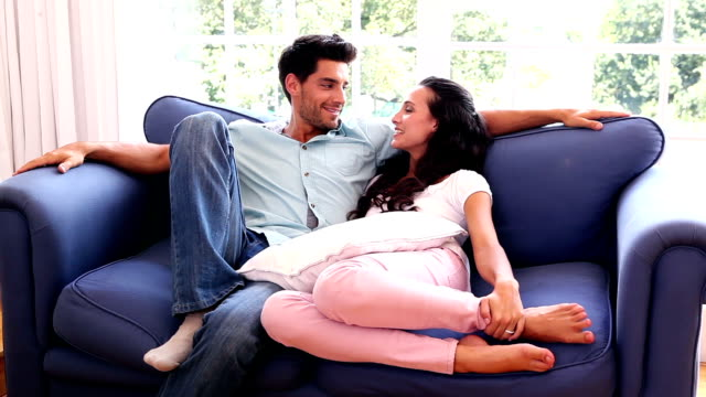 Attractive couple chatting on the couch video